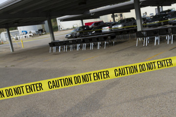Yellow do not enter caution tape stretched across a parking lot with tables and chairs set for a company picnic.