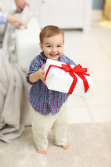 Cute baby with gift box in the room