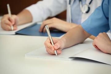 doctors hands writing at table closeup