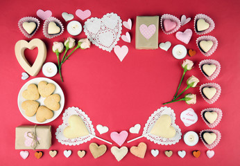 Set of hearts shapes cookies and candies on red table, top view