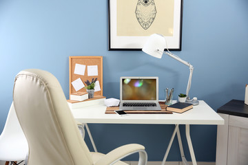 Workplace with laptop, mobile phone and table on blue wall background