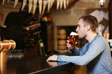 Young man drinking beer in a bar