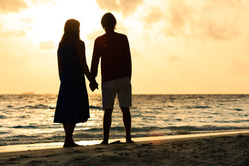 romantic couple holding hands at sunset