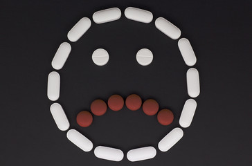 Pills in form of a frown face