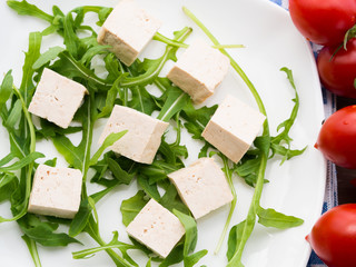 Vegan food concept with tofu, arugula and tomatoes