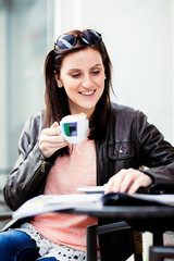 Young brunette woman sitting at a coffeeshop and relaxing