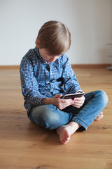 boy sitting on the wooden floor and reading electronic book