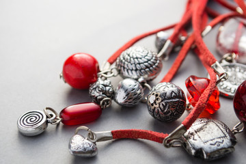 Close up of red glass beads and silver charms