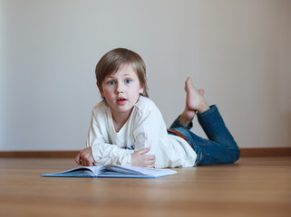 boy lying on the wooden floor and reading book