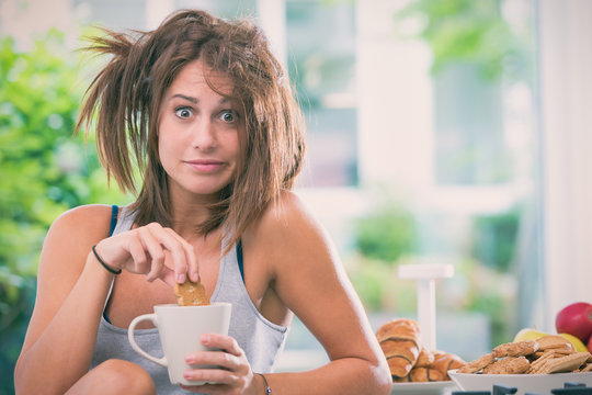 Young messy woman have breakfast in the kitchen