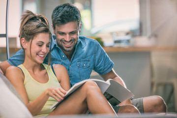 Young couple read a magazine seated on couch indoor
