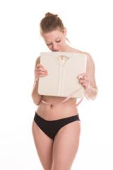 Jeune femme avec une culotte noir sur fond blanc tenant une balance