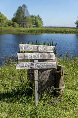 'Do not feed that Gators' wooden sign post, beside a lake in the American deep south