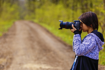young photographer who takes pictures in forest