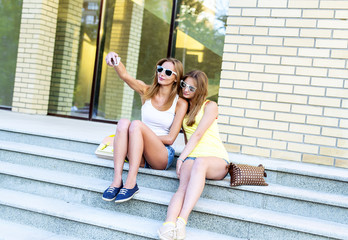 Two sisters on steps of the institute are doing self, social networking, glasses and denim shorts.