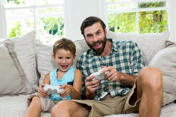 Portrait of father and son playing video game at home