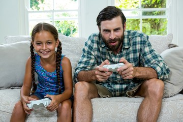 Portrait of father and daughter playing video game at home
