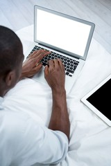 Young man lying on bed and using laptop