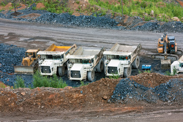 Bulldozer, dump trucks and excavator at the bottom of the quarry