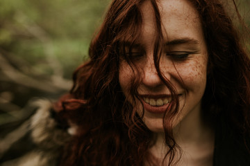 Closeup of a redhead teen woman in the forest