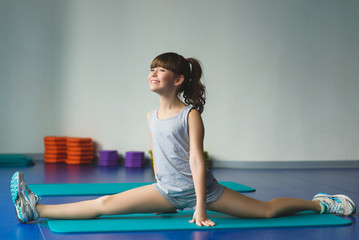 Girl sat and makes stretching or gymnastic exercises in the class for fitness