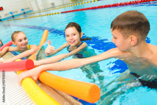 happy and smiling group of children learning to swim with pool noodle stockfotos und. Black Bedroom Furniture Sets. Home Design Ideas