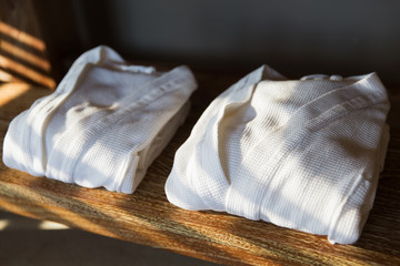 close up of two white bathrobes on wooden shelf