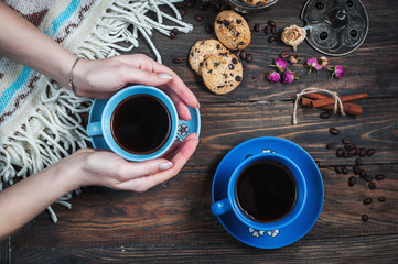 Hands take cup of coffee, coffee beans and cookies-hearts