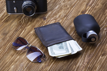 gentlemanly set:  sunglasses, perfume, wallet, money,camera on wooden background