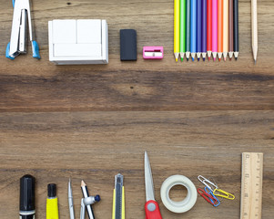 Business concept:stapler,color,pencil,divider,rubber,pencil,glue,sharpener,tape and pen on wooden plank background