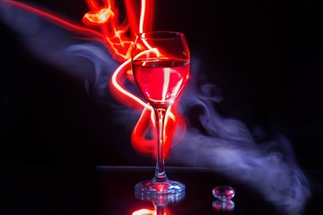 Glass of wine and red light painting