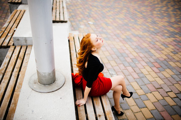 Girl sits on the bench in the red skirt