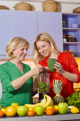 Mother and daughter blending broccoli and baby spinach for smoothie