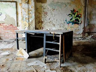 Abandoned old grungy vintage wooden desk indoors in crumbling room - landscape color photo