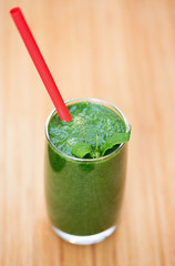 A glass of green smoothie with tube on wooden background