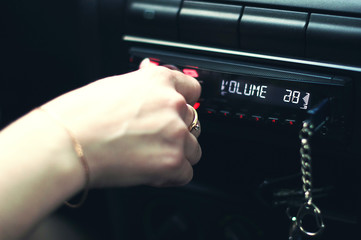 hand pushing power button to turn on  car stereo system.