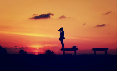 The silhouette of photographer with sunset background