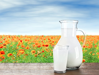 Pitcher, glass of milk on wooden table against poppies and blue sky background