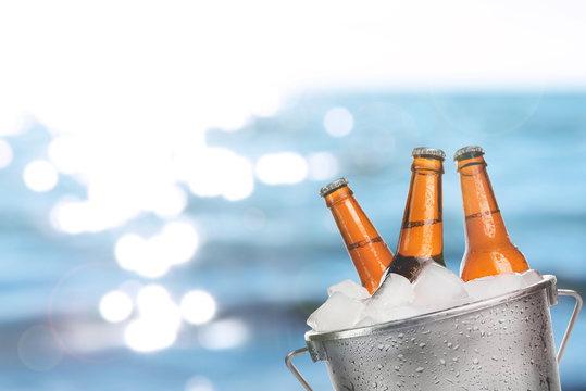 Beer bottles of cold fresh beer in ice bucket, on sea or ocean background