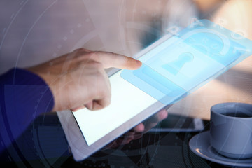 Man working with tablet-pc and icon security on virtual display. Technology, internet and networking concept.