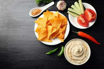 Ceramic bowl of tasty hummus with chips and chili on table