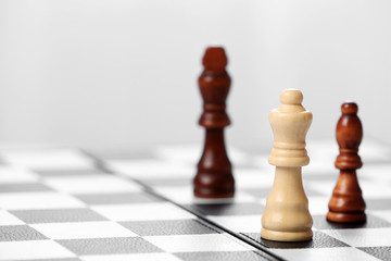 Chess pieces and game board on light blurred background
