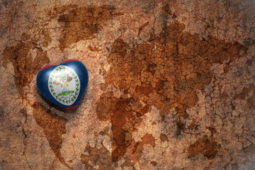 heart with national flag of belize on a vintage world map crack paper background. concept