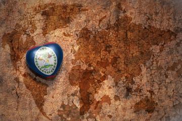 heart with national flag of belize on a vintage world map crack paper background. concept