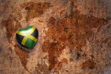 heart with national flag of jamaica on a vintage world map crack paper background. concept