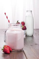Strawberry milkshake, strawberries and milk bottle.