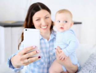Beautiful woman make selfie on mobile phone with baby boy in room