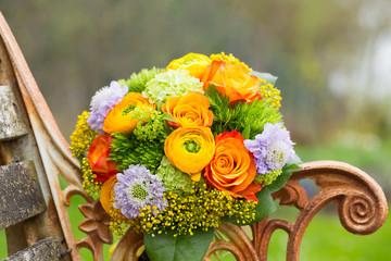 Wunderschöner Blumenstrauß auf alter Holzbank im Garten