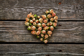 Rose flowers in heart shape on wooden plates