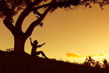 Happy young man outdoors with arms up in the air looking at the sunset.